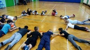 Grupa dzieci leży na brzuchu w sali gimnastycznej tworząc koło i trzymając się za ręce