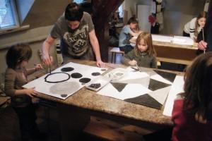 Grupa dzieci z opiekunem stoi przy stole i maluje
