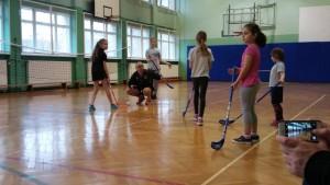 Grupa dzieci gra w hokeja na sali gimnastycznej
