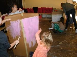 Grupa dzieci maluje farbami duże stojące kartony
