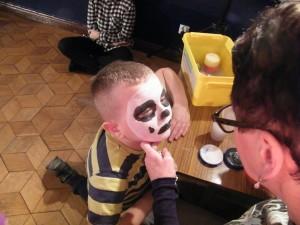 Kobieta maluje twarz dziecka, który stoi przed nią
