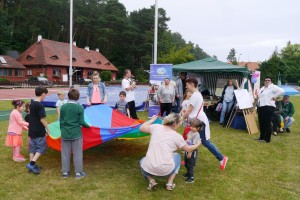 Grupa dzieci i kobiet stoi w okręgu i trzyma ogromną kolorową chustę