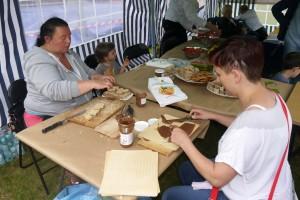 Dwie Panie siedzą przy stole na przeciwko siebie i smarują wafle kremem orzechowym