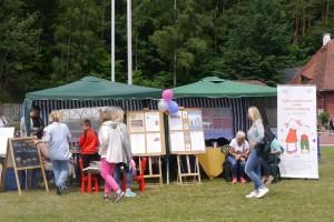 Kilka osób stoi przed namiotami w których znajduje się punkt informacyjny. Na pierwszym planie stoją na szatalugach tablice z plakatami