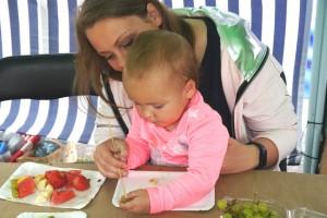 Kobieta siedzi przy stole z małym dzieckiem, które trzyma na kolanach i pomaga mu nabić winogrono na patyczek