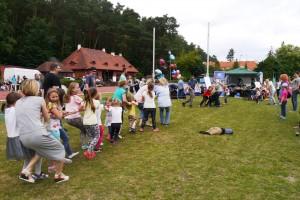 Gruopa dziewczynek stoi na przeciwko chłopców i przeciągają linę, którą trzymają w rękach