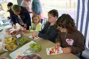 Grupa dzieci siedzi przy stole na którym stoją różne owoce i nadziewają owoce na patyczki