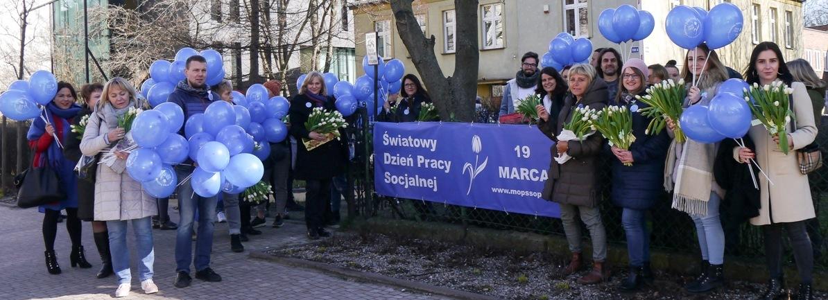 Grupa osób z niebieskimi balonami i białymi tulipanami stoi przy drzewie obok płotu