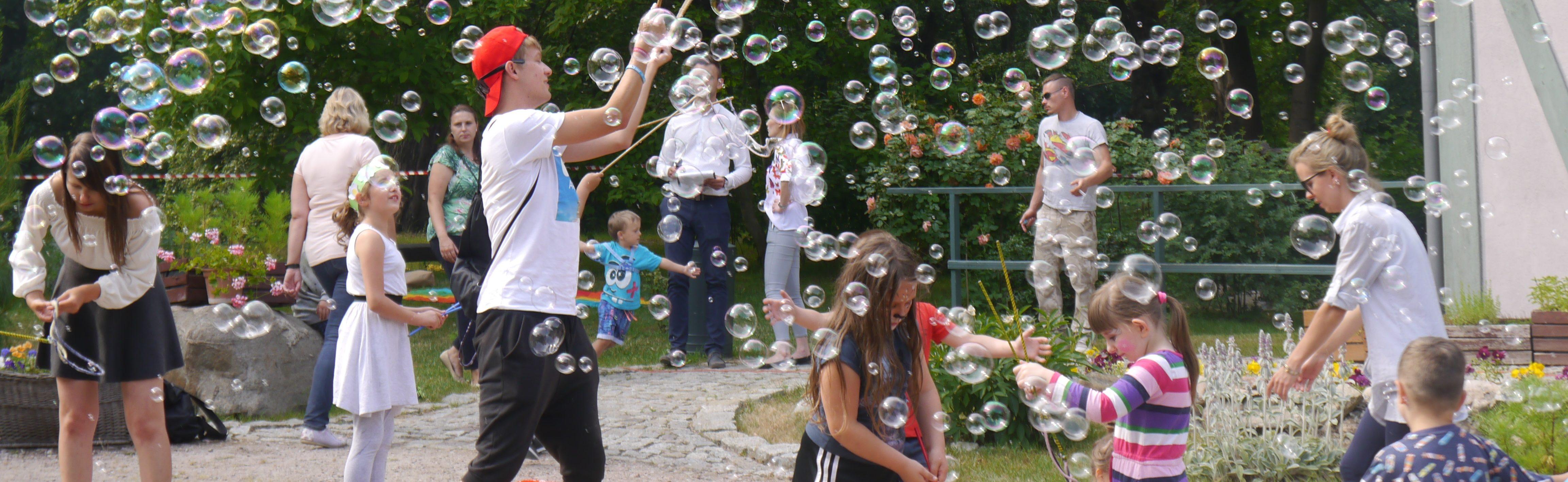 Grupa osób wraz z dziećmi puszcza duże bańki mydlane