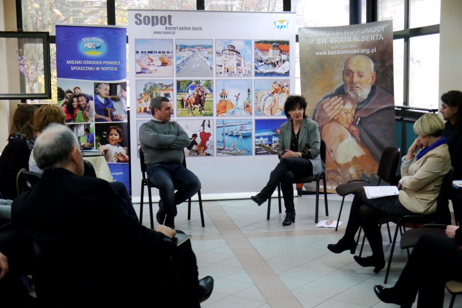 Wiceprezydent Sopotu siedzi naprzeciwko uczestników spotkania i rozmawia z zaproszonym Syryjczykiem Samer Samaan