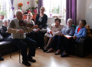 Pan Tadeusz gra na skrzypcach, pozostali uczestnicy siedzą na kanapach i słuchają