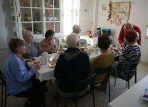 Uczestnicy Środowiskowego Domu Samopomocy siedzą w kuchni przy stole i jedzą posiłek