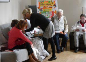 Grupa seniorów siedzi na kanapach, kierowniczka przykrywa jedną z uczestniczek kocem