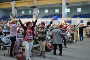 Grupa seniorek ćwiczy na hali targowej podnosząc ręce do góry