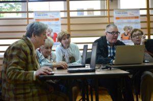 Grupa seniorów uczy się obsługi komputera