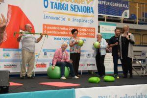 Grupa seniorów ćwiczy z piłkami na scenie