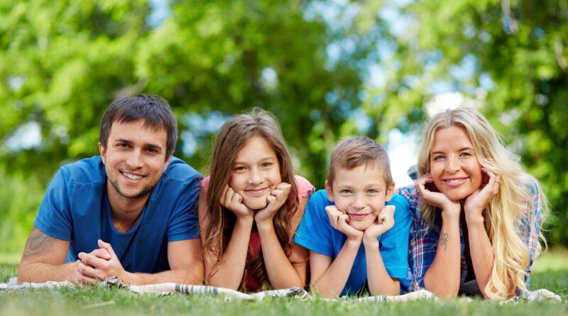 Uśmiechnięta rodzina leży na trawie