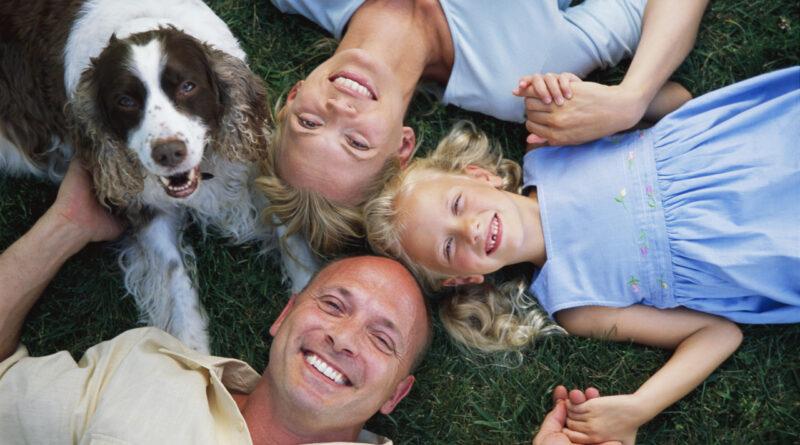 Rodzice z dziewczynką i psem leżą na trawie