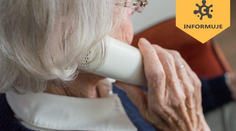 starsza pani trzyma w ręku słuchawkę telefoniczną