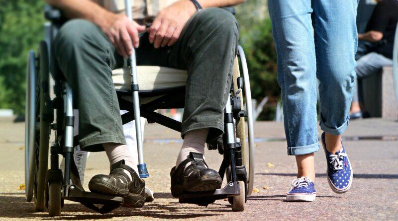 mężczyzna siedzi na wózku inwalidzkim, obok stoi kobieta