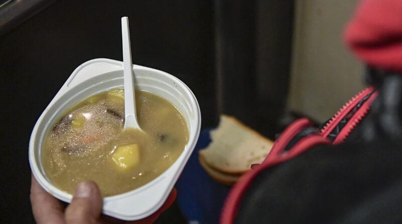 mężczyzna trzyma w dłoni talerz zupy oraz chleb