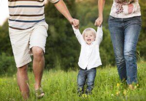 mężczyzna i kobieta trzymają za ręce małe dziecko