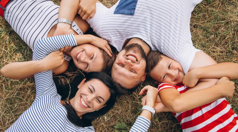 rodzice z dziećmi leżą na trawie