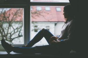 kobieta siedzi na parapecie i patrzy w okno