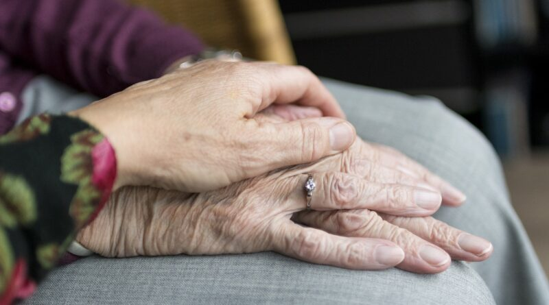 kobieta położyła dłoń na dłoni starszego mężczyzny