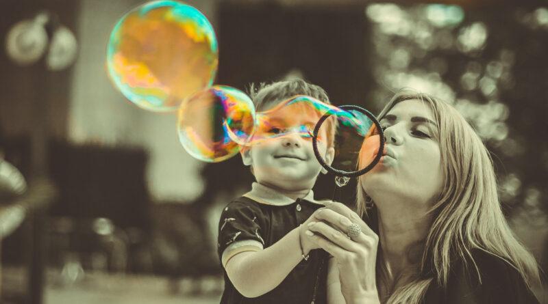 kobieta z synem dmucha bańki mydlane