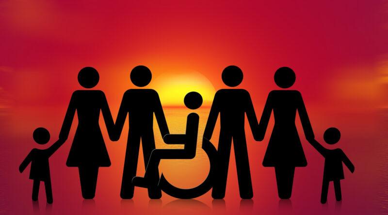 ludzie trzymają się za ręce, w środku osoba na wózku