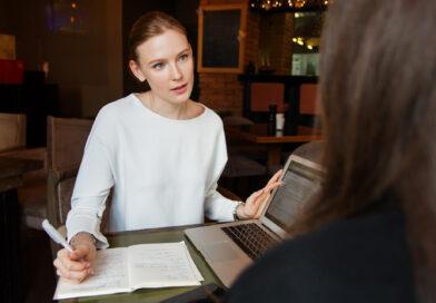 kobieta rozmawia z osobą, która siedzi naprzeciwko