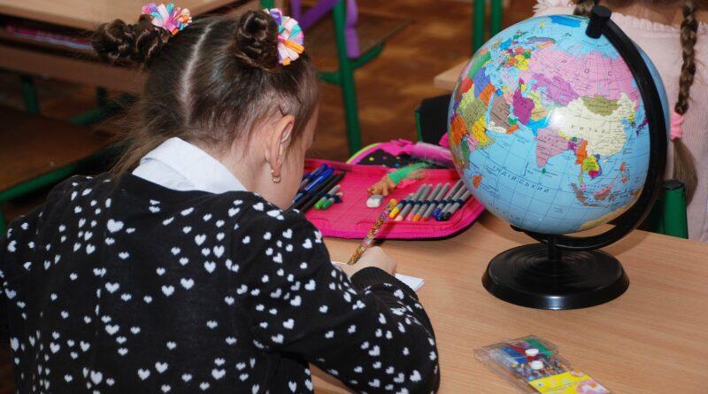 dziewczynka siedzi tyłem przy biurku