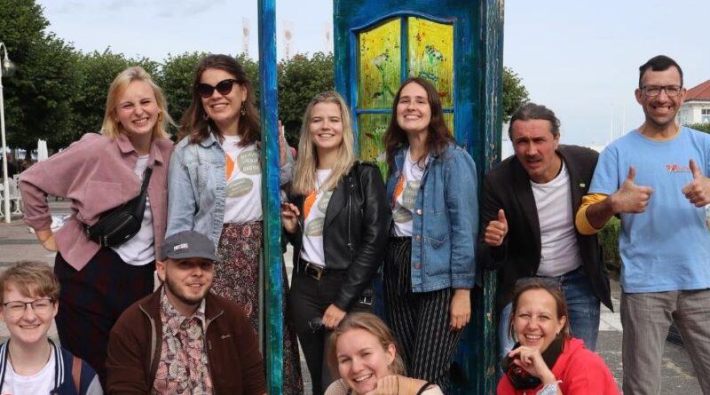 grupa osób stoi w otwartych drzwiach