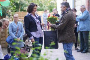 mężczyzna wręcza kobiecie kwiaty oraz torbę z upominkami